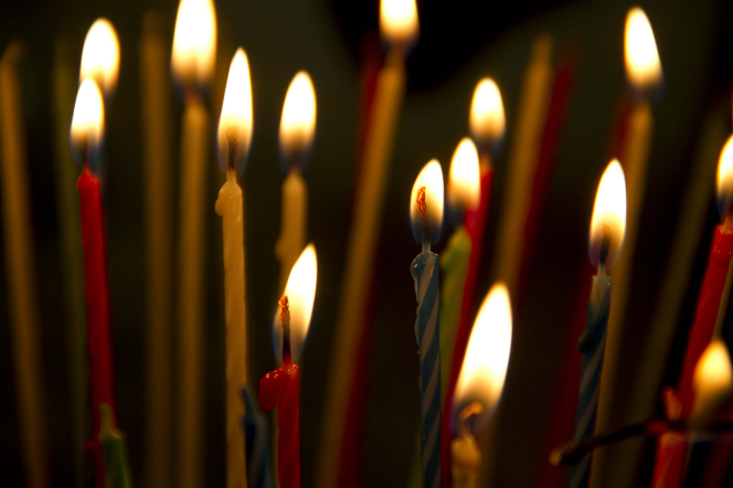 A close-up view of red, yellow, blue, and green birthday candles burning in the dark.