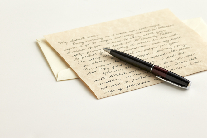 A brown pen lying on top of a handwritten letter and an envelope.