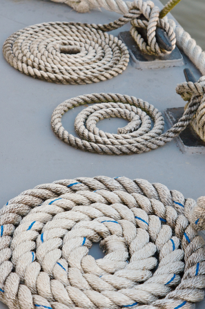 Three thick tan ropes coiled on a boat deck.