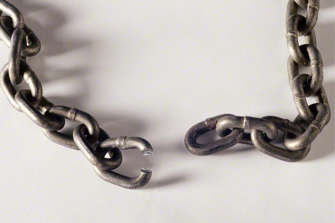 A heavy metal chain against a white background, shown with one link broken, which has separated the entire chain.