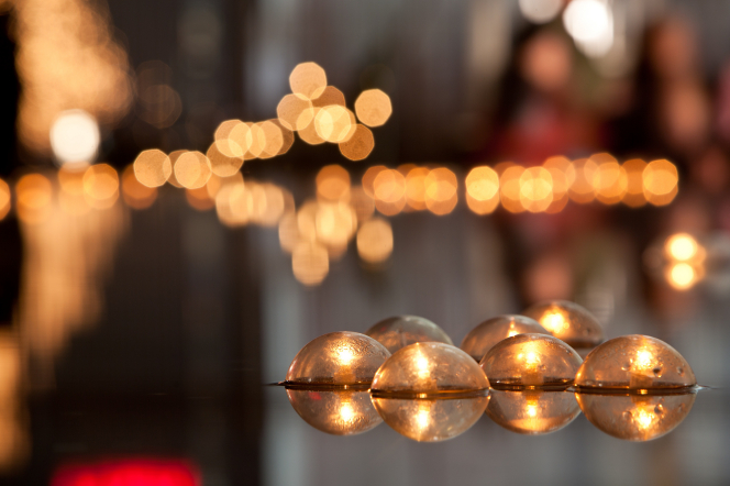 A group of seven small candles floating on a pool at Christmastime, with the blurred lights of many other candles seen in the distance.