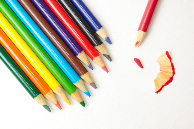 Eleven colored pencils lying on a white background together, except for one which is broken and sitting apart from the others.