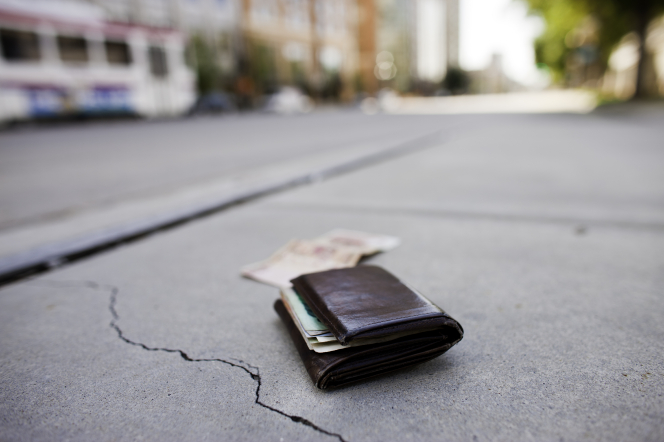 A man's leather wallet lying on a cracked sidewalk, with a bill of money in front of it on the concrete and a city train blurred in the background.