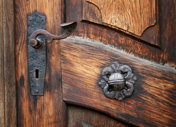 A old brown wooden door with two worn metal knobs fashioned in different shapes on the left side of the door.