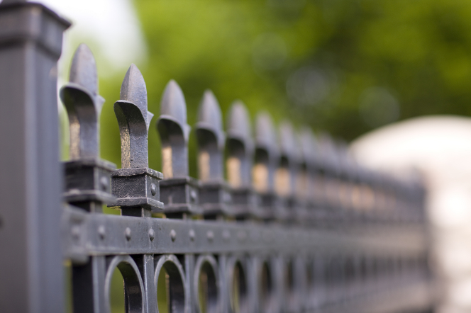 A long row of the decorative tops of the posts on a black iron fence blurring out toward the end of the row.
