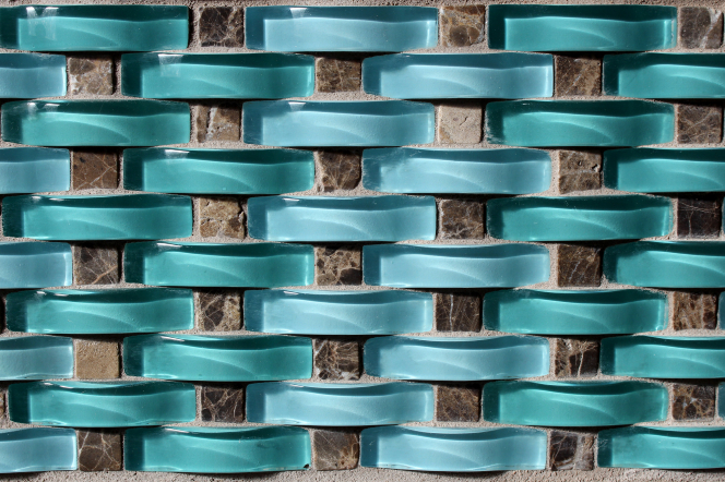 Curved sections of aqua-colored glass set between gray squares of tile-like cement.