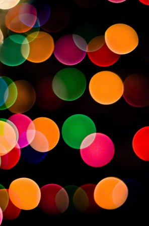 Green, yellow, pink, red, and blue circles of blurred light on a black background.