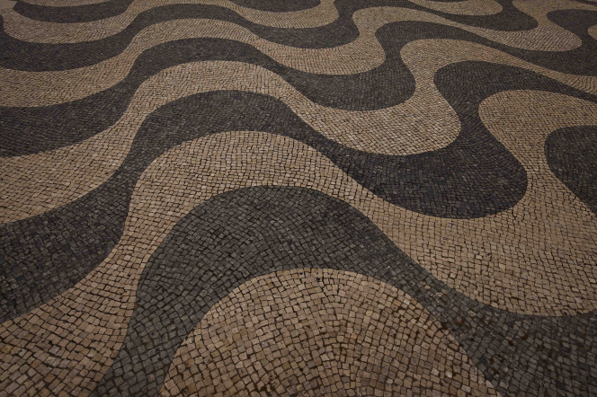 A black and tan wave pattern on the ground, formed like a mosaic out of small stones set into a path.