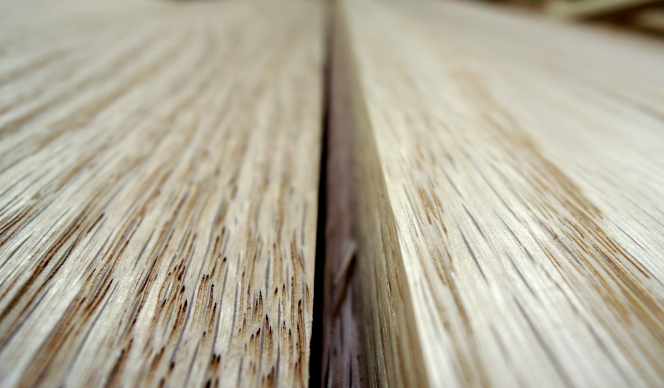 A narrow band of detail of two wooden boards close together, showing some of the pores in the wood and the space between the two boards.
