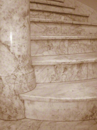 A white marble staircase turning once around a column made of the same marble.