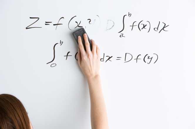 A woman's hand erasing a math equation from a whiteboard, where it was written in black dry-erase marker.