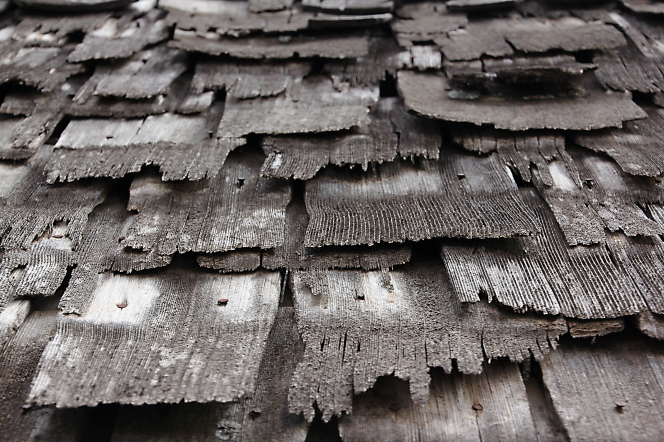 Tattered wooden shingles nailed to a slanted roof in a somewhat random pattern.