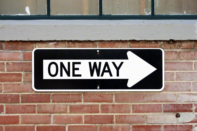 "A black and white sign with the words ""One Way"" and a large arrow pointing to the right, hanging on a red brick wall under an old window."