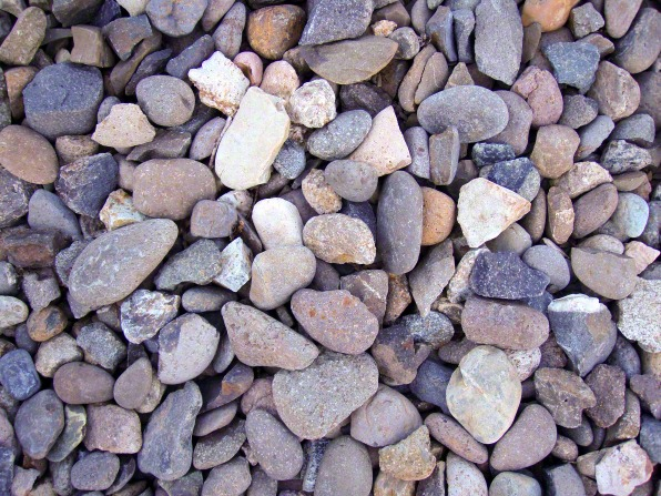 Small and medium-sized gray, brown, and white rocks are piled on one another, interspersed with a few twigs.