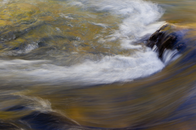 A view of dark green, blue, and yellow waves coming over the rocks in a swift river.