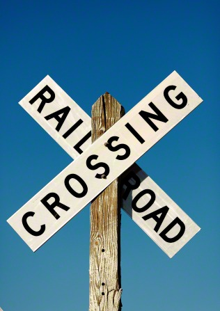 A black and white railroad crossing sign in the shape of an x against a clear blue sky.