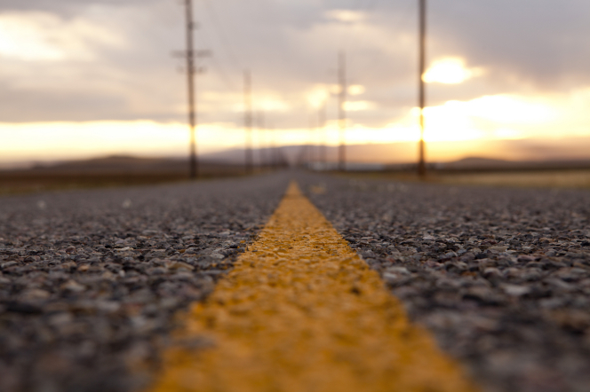 A detailed view of the yellow painted line running down the middle of an asphalt road, blurring out in the background toward a sunset on the horizon.