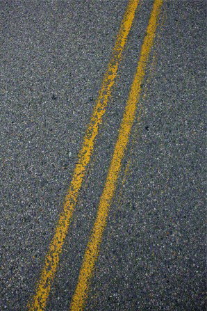 Two faded yellow paint lines running parallel on a dull gray asphalt road.