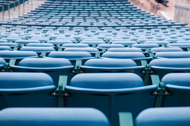 Blue folding seats in an outdoor theater or stadium setting, looking from the back toward the front.