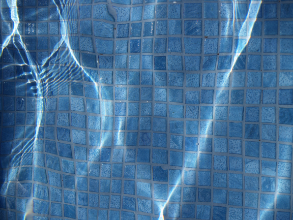 Small blue tiles from the bottom of a swimming pool or water fountain, seen distorted through three vertical ripples of water above them.