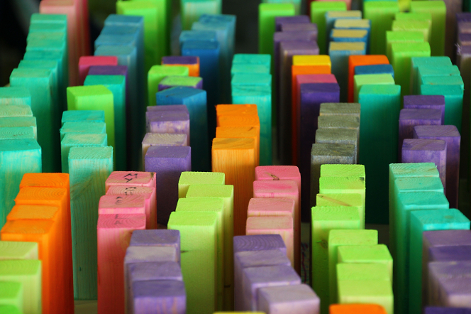 Small wooden pieces painted green, purple, blue, orange, and pink standing on end in messy rows.