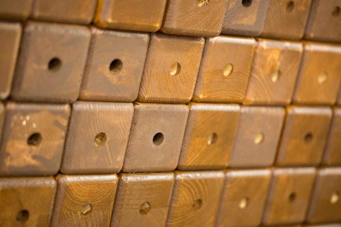 Four or so rows of wooden beams with rounded corners and holes drilled into them, stacked to form a pattern.