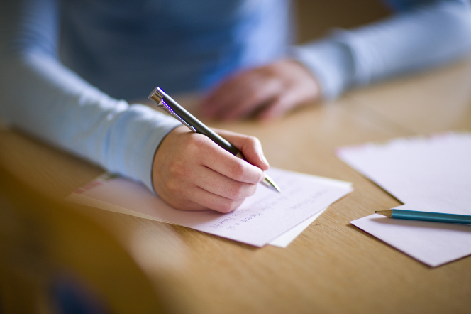 A young woman's hand holding a pen over a piece of loose-leaf stationery paper on a wooden table.