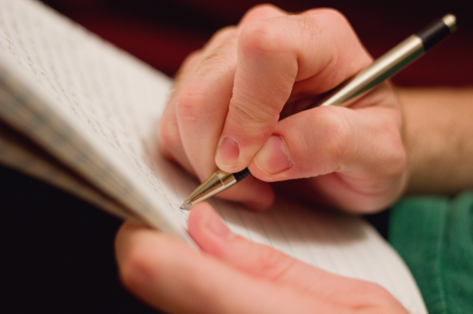 A young man's hand with short nails, holding a silver and black pen and writing in a lined notebook.