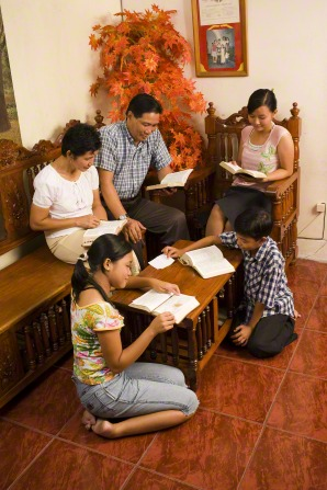 Five family members sit together on wooden benches and chairs, reading the scriptures.