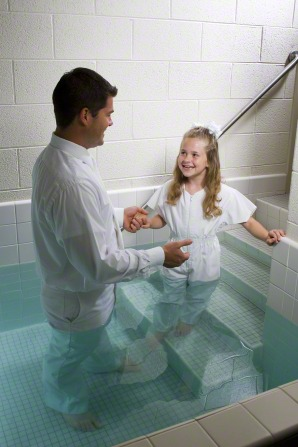 A young girl in a white jumpsuit walks toward her father, who is standing in a baptismal font.