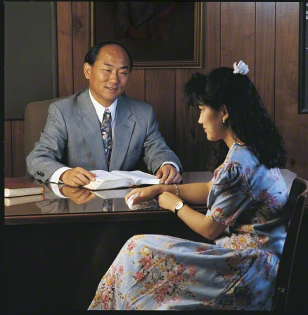 A young woman in a floral print dress sits in front of her bishop, who has a set of scriptures open in front of him.