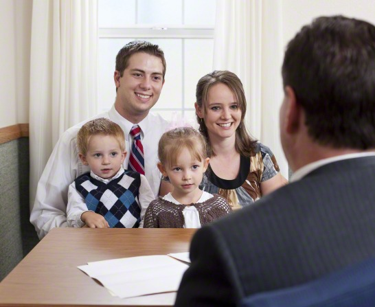 A young family of four sits in the bishop's office, smiling and talking to him about their tithing for the year.
