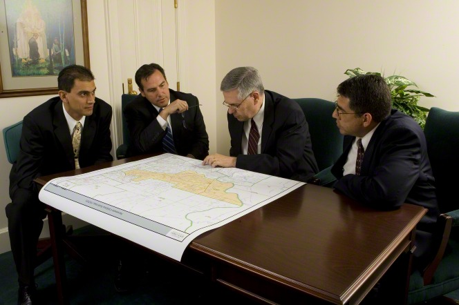 Four men in black suits sit at a wooden desk and look at a map.