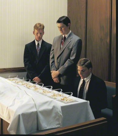 Two young men in suits stand near a sacrament table with their heads bowed while a third offers the prayer for the sacrament bread.