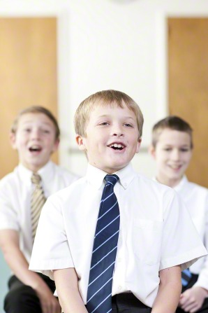 Three Primary-age boys sit in a Primary room in white shirts and ties and sing together during singing time.