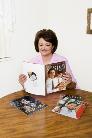 A woman with short brown hair sits reading the Ensign at a table that has several Church magazines on it.