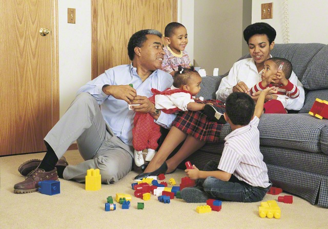 A mother and father sitting in their living room, surrounded by their four young children, playing with blocks and talking.