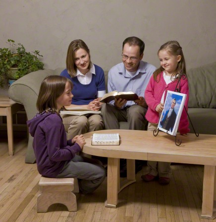 A family of four sitting together, looking at a painting of Joseph Smith from the Gospel Art Book.
