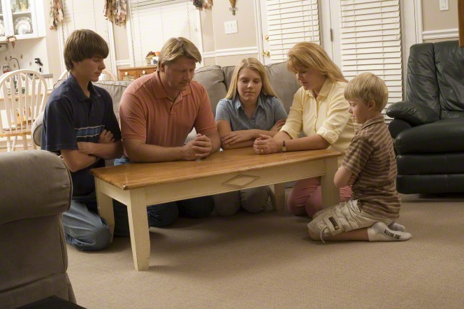 Two parents and their three children kneel around a small table with their heads bowed to pray before bedtime.