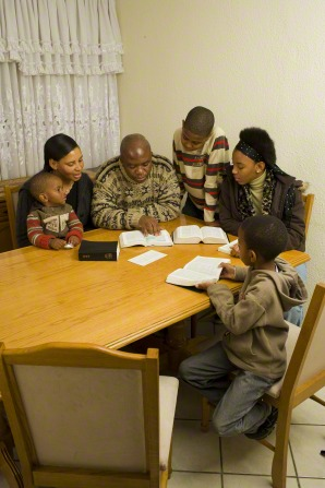 Six family members sit together at the kitchen table, reading from the Book of Mormon.