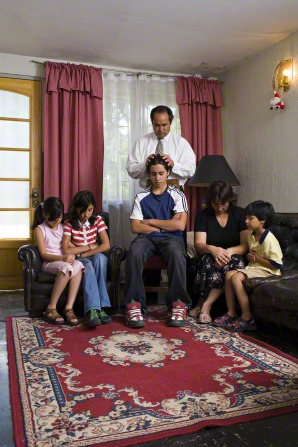 A father in a white shirt and tie gives a blessing to his son while the other family members bow their heads and listen.