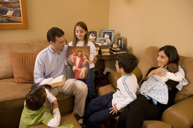 A couple and their four children sit in their living room and look at a picture of Christ with children during their family home evening.