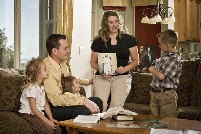 A mother and her son hold pictures of Jesus Christ and Joseph Smith while teaching a family home evening lesson to the rest of the family.