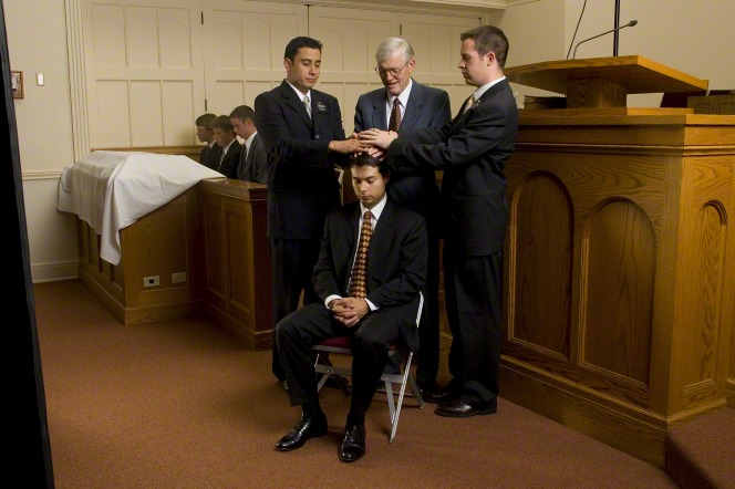 A young man in a black suit is given the gift of the Holy Ghost by three other men in a sacrament meeting setting.