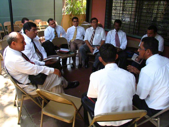 A group of 10 men in white shirts and ties sit in a circle, discussing a lesson from a Teachings of Presidents of the Church manual.