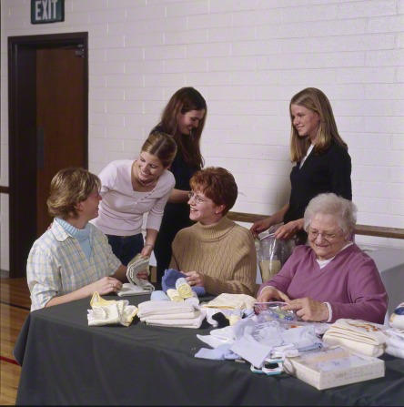 A group of six Relief Society women sit in the cultural hall at a church to make hygiene kits as a service project.