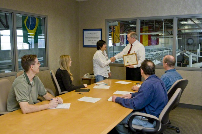 A woman stands in a boardroom and shakes the hand of a man who is presenting her with a certificate.