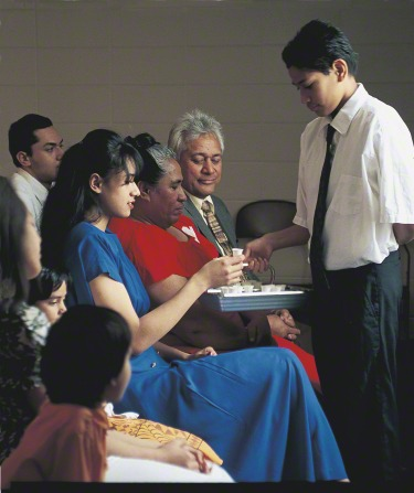 A deacon in a white shirt and tie is holding out the water sacrament tray to a young woman in a blue dress, who is holding a sacrament cup.
