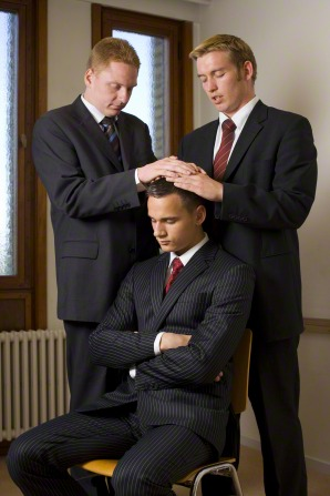 Two men in black suits lay their hands on the head of another man to give him a priesthood blessing.