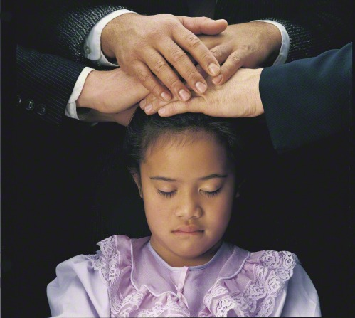 A young black-haired girl in a purple dress closes her eyes while three men place their hands on her head, confirming her a member of the Church.